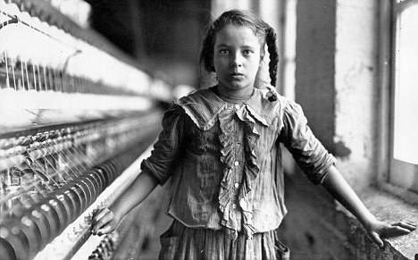 Portrait of a child laborer standing between a spinning loom and a window at a cotton mill. The young girl wears tattered work clothes. North America 1909